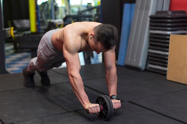 腹部の車輪で運動を行う筋肉の若い男