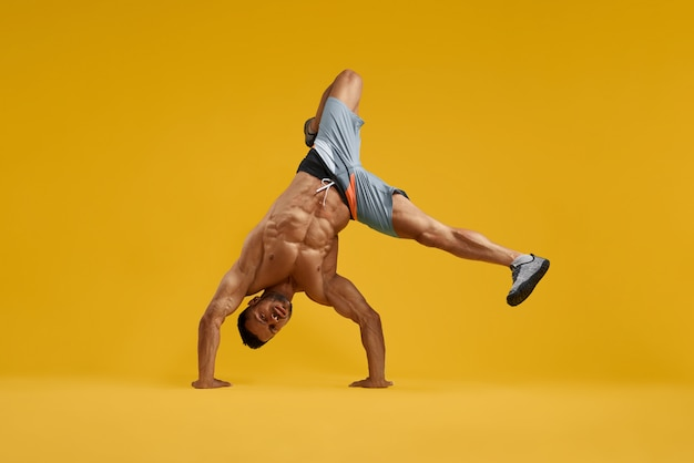Muscular young man performing handstand stunt