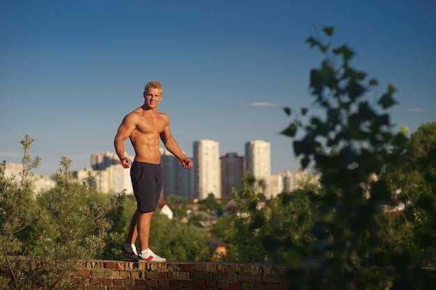 지붕 꼭대기에 서서 일몰 동안보고 근육 질의 젊은 남자. 건강한 라이프 스타일과 자신감의 개념.