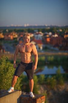 Мускулистый молодой человек, стоящий на крыше и смотрящий во время заката. концепция здорового образа жизни и уверенности.