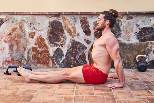 Muscular young man stretching at home. home workout concept and healthy living.