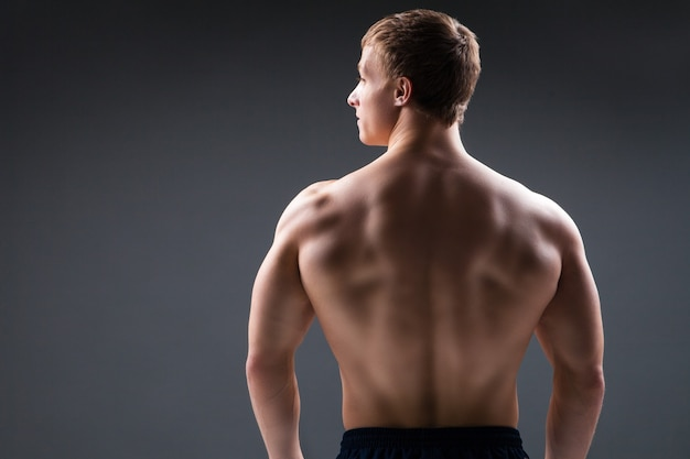 Muscular young man in studio on dark background shows the different movements and body parts. back view