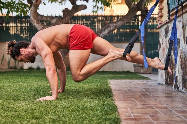 弾性バンドを自宅でトレーニング筋肉の若い男。ホームトレーニングのコンセプトと健康的な生活。