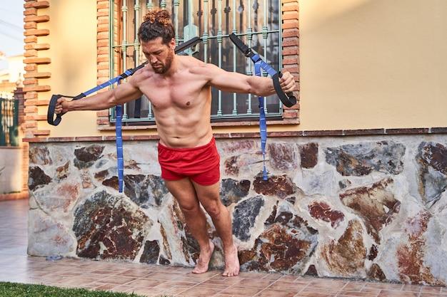 筋肉の若い男がゴムバンドで自宅でトレーニングします。ホームトレーニングのコンセプトと健康的な生活。