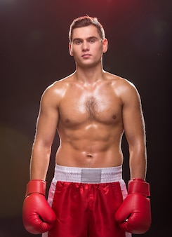 Muscular young man with boxing gloves on the dark.