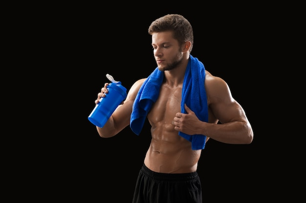 Muscular young man with a towel drinking water after exercising at the gym