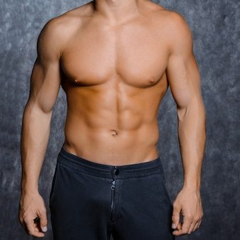 Muscular young sexy man  in a cap with a naked torso on black background
