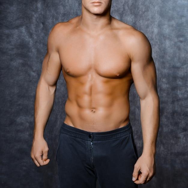 Мускулистый молодой сексуальный мужчина в кепке с голым торсом на черном пространстве