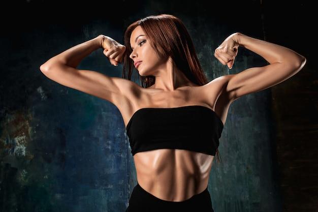 Atleta muscolare della giovane donna sul nero
