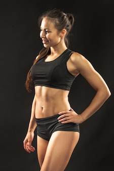 Muscular young woman athlete looking in camera on black