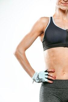 Мускулистый спортсмен молодой женщины на белом