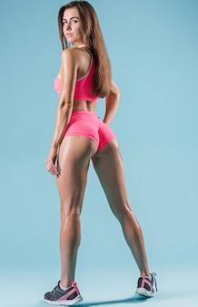 青い背景の上のスタジオでポーズをとって筋肉の若い女性アスリート