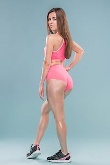 青い背景のスタジオでポーズをとって筋肉の若い女性アスリート