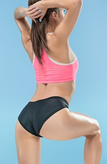 青のスタジオでポーズをとって筋肉の若い女性の運動選手
