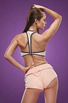 Мускулистая молодая женщина-спортсмен позирует в студии на сиреневом фоне