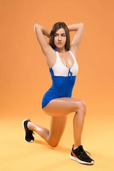 オレンジ色の背景のスタジオでポーズ筋肉の若い女性アスリート
