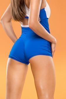 オレンジ色の背景のスタジオでポーズをとって筋肉の若い女性アスリート