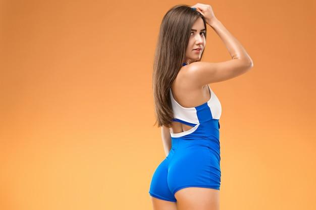 オレンジのスタジオでポーズ筋肉の若い女性アスリート