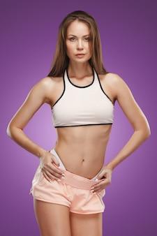 スタジオでポーズ筋肉の若い女性アスリート