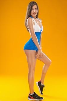 スタジオでポーズ筋肉の若い女性の運動選手