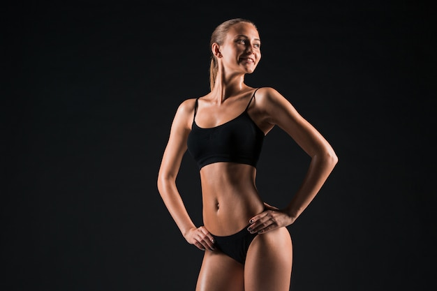 Muscular young woman athlete posing on black