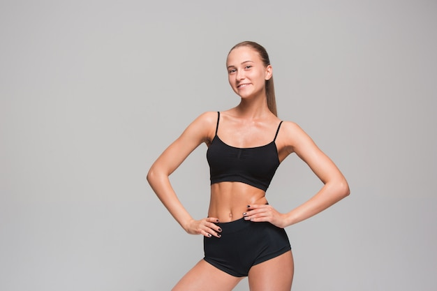 Muscular young woman athlete posing on gray