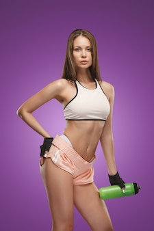 Muscular young woman athlete posing on lilac space with drink water