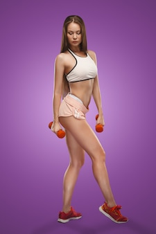 Muscular young woman athlete posing on lilac space with dumbbells