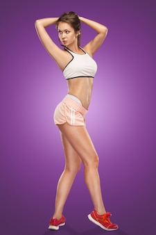 Muscular young woman athlete posing on lilac space