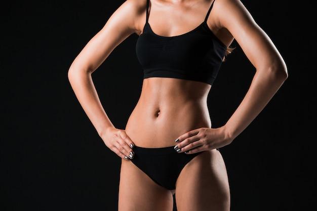 Мускулистая молодая женщина-спортсмен позирует на фоне черной студии