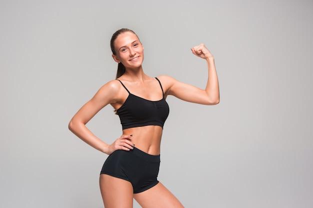 Мускулистые молодая женщина спортсмен позирует на серый
