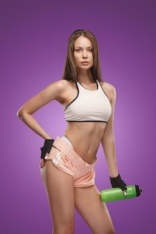 Мускулистые молодая женщина спортсмен позирует на сиреневом пространстве с водой пить