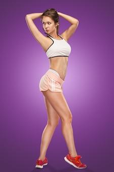 Мускулистые молодая женщина спортсмен позирует на сиреневом пространстве