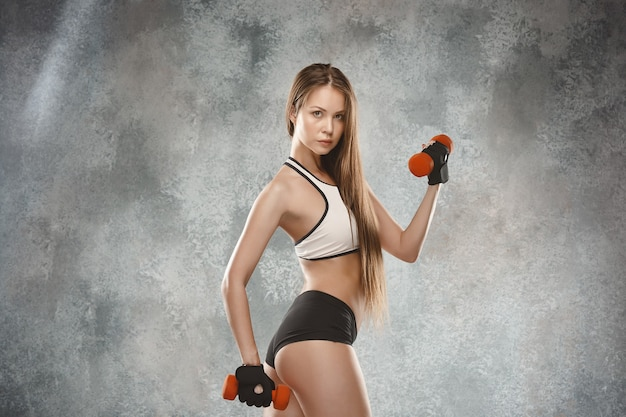 Muscular young woman athlete posing at studio with dumbbells