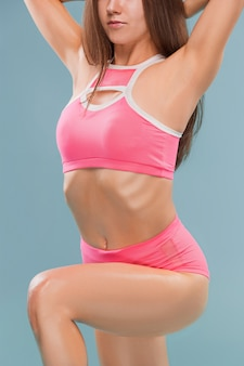 Muscular young woman athlete posing at studio