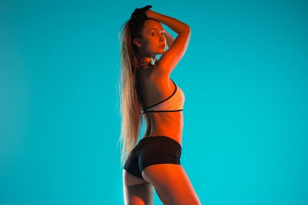 Мускулистые молодые женщины спортсмен позирует