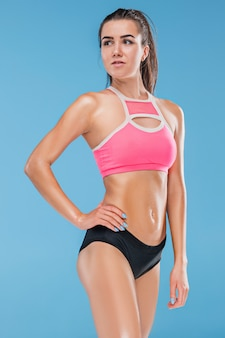 Muscular young woman athlete posing
