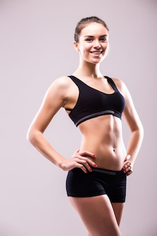 Muscular young woman athlete standing looking down with her hands on hips on grey wall