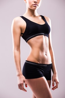 회색 벽에 엉덩이에 그녀의 손으로 아래를 내려다 보면서 서 근육 질의 젊은 여자 선수