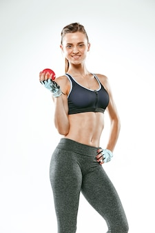 Muscular young woman athlete standing on white background with apple.