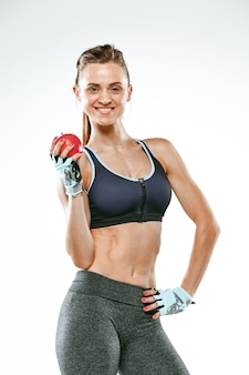 Muscular young woman athlete standing on white with apple.