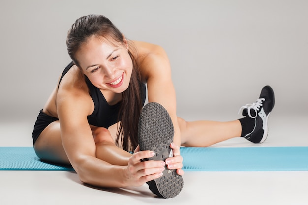Muscular young woman athlete stretching on gray