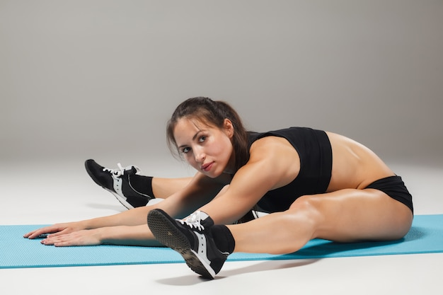 Muscular young woman athlete stretching