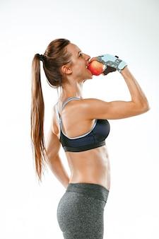 Atleta muscolare della giovane donna su bianco