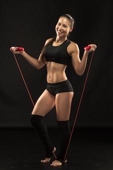 블랙에 건너 뛰는 밧줄으로 근육 질의 젊은 여자 선수