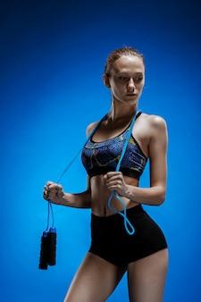 Мускулистые молодая женщина спортсмен со скакалкой на синем