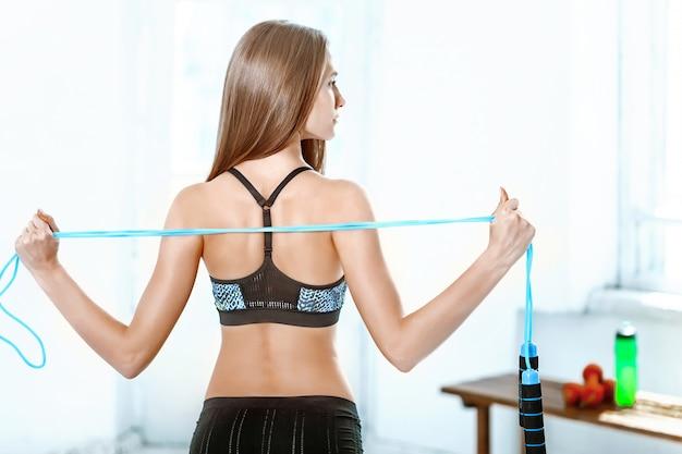Мускулистые молодая женщина спортсмен со скакалкой на белом