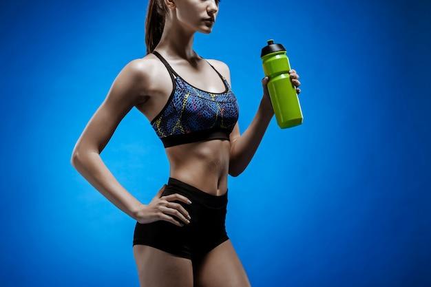 青の水で筋肉の若い女性アスリート
