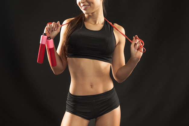 Muscular young woman athlete with a skipping rope on black