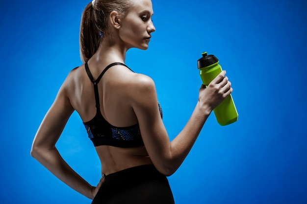 Muscular young woman athlete with a water on blue